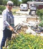 Danielle Delhomme waters flowers in the community garden she helped develop at First Central Presbyterian Church. When completed, the garden will provide fresh vegetables for neighbors. The garden is landscaped with flowers, shrubs, a stone cross and patio area.