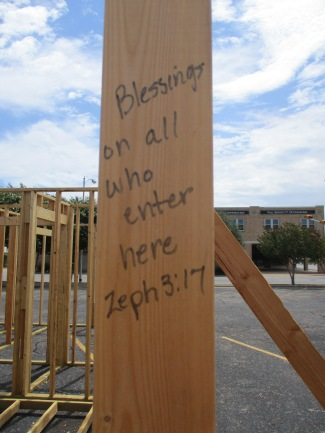 Blessings are written on the framework of a new Habitat for Humanity house under construction in the parking lot of First Baptist Church.