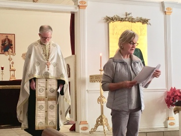 Linda Fowler chants a reading at St. Luke Orthodox Church, with Father Philip LeMasters in back. Photo by Loretta Fulton