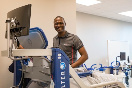 A member of the Kenya delegation tries Physical Therapy equipment