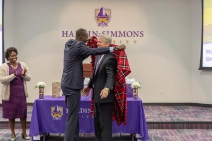 HSU President Eric Bruntmyer receives a traditional Masaai Shuka cloth.